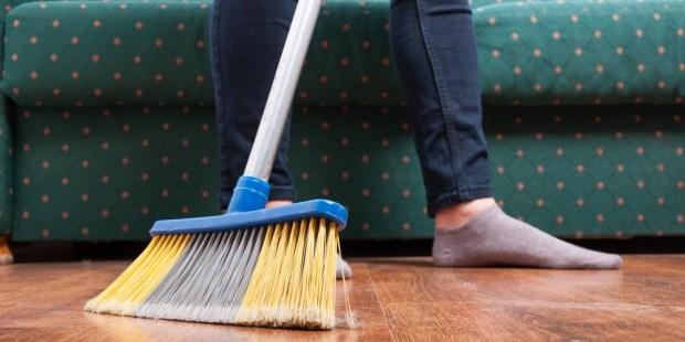 Woman sweeping wooden floor