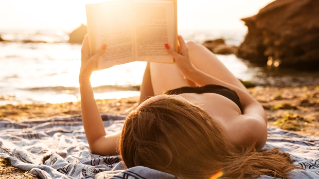 WOMAN READING BEACH
