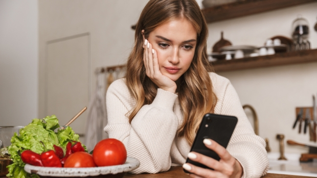 WOMAN LOOKING AT PHONE WHILE COOKING